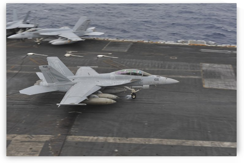 An F-A-18F Super Hornet lands on the flight deck aboard USS Nimitz. by StocktrekImages
