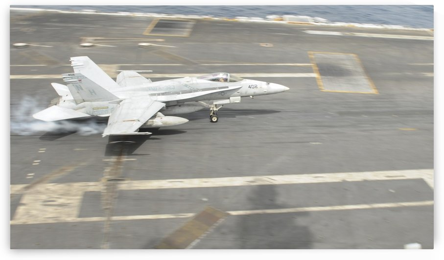 An F-A-18C Hornet lands on the flight deck of USS Nimitz. by StocktrekImages