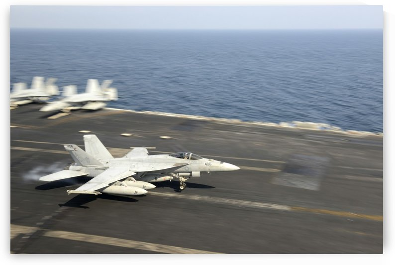 An F-A-18E Super Hornet lands on the flight deck of USS Harry S. Truman. by StocktrekImages