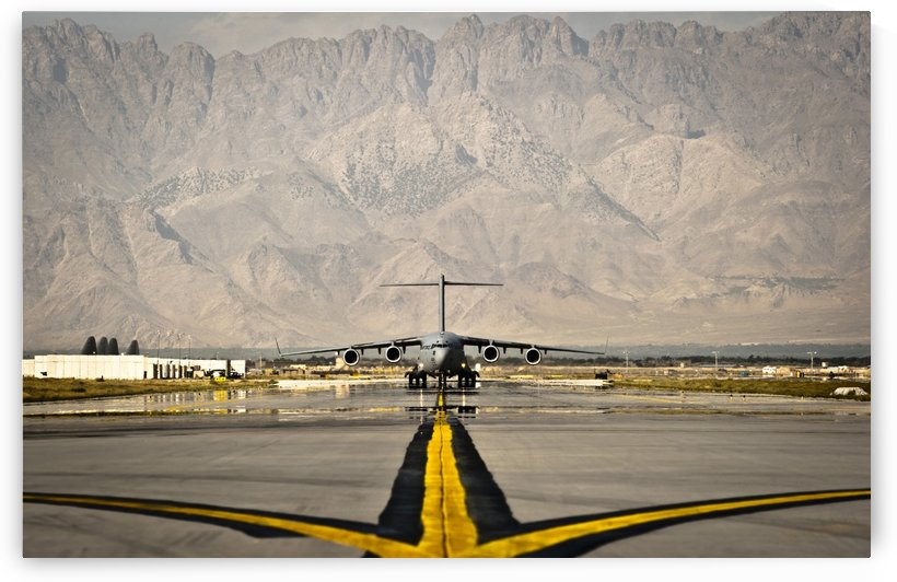 A C-17 Globemaster III taxis to its parking spot at Bagram Airfield. by StocktrekImages