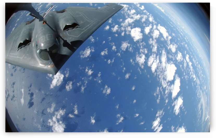 A KC-135 Stratotanker refuels a B-2 Spirit over the Pacific Ocean. by StocktrekImages