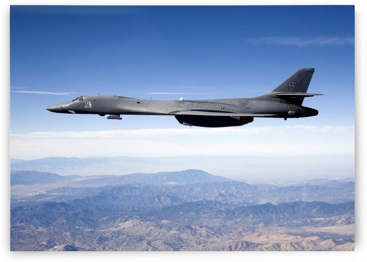 A B-1B Lancer carries the Sniper pod on its belly as it flies through the sky. by StocktrekImages