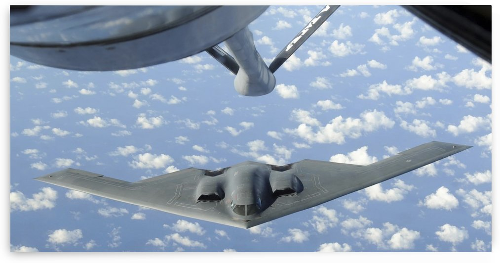 A B-2 Spirit approaches the refueling boom of a KC-135 Stratotanker. by StocktrekImages