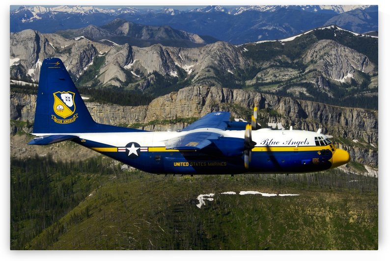 A C-130 Hercules Fat Albert plane flies over the Chinese Wall rock formation in Montana. by StocktrekImages