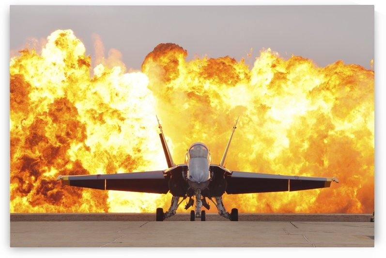 An F-A-18 Hornet sits on the flight line as a wall of fire detonates behind it. by StocktrekImages