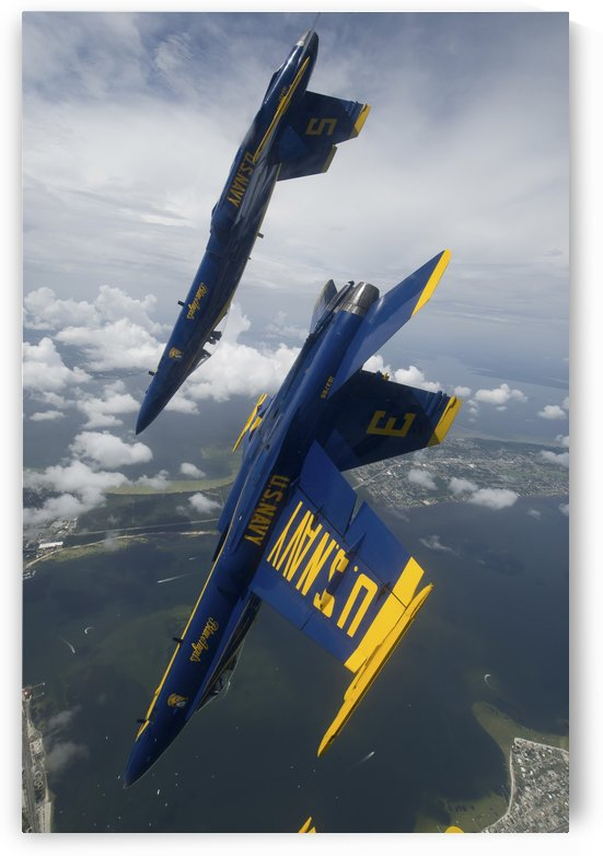 The Blue Angels perform a looping maneuver over Pensacola Beach Florida. by StocktrekImages
