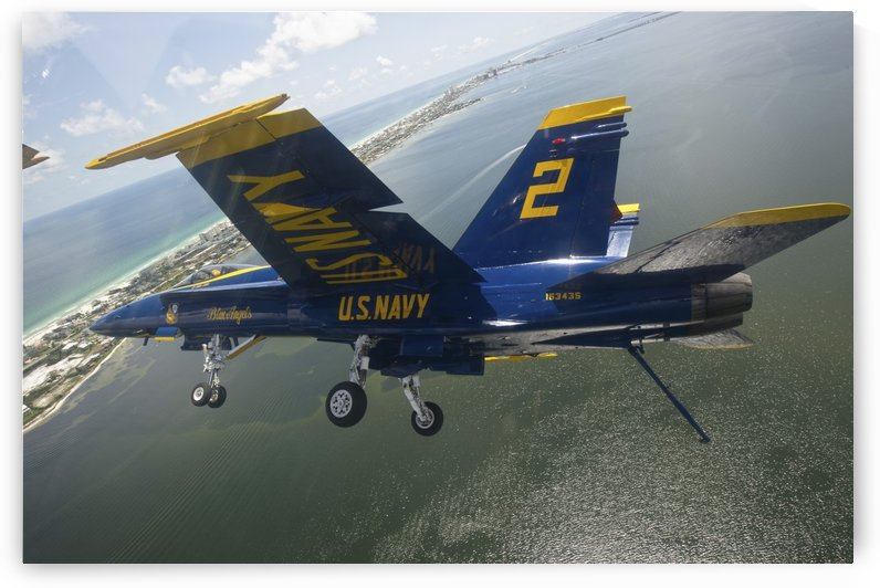 An F-A-18 Hornet of the Blue Angels in flight over Pensacola Beach Florida. by StocktrekImages