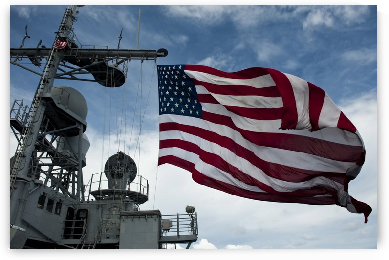 USS Cowpens flies a large American flag during a live fire weapons shoot. by StocktrekImages