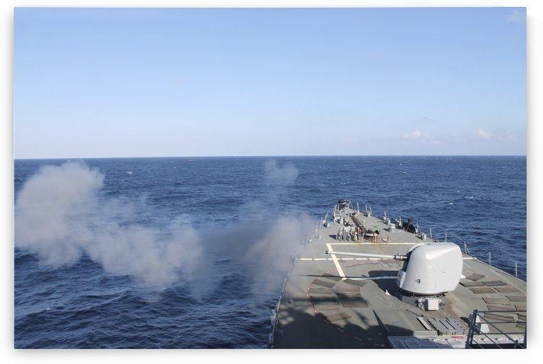 USS Mahan fires a 5-inch gun during a training exercise. by StocktrekImages