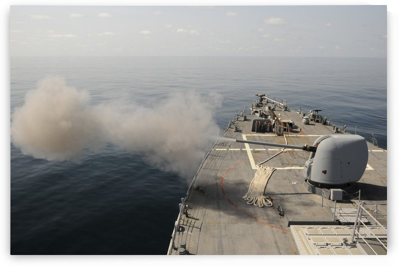 An Mk-45 lightweight gun is fired aboard guided missile destroyer USS Mitscher. by StocktrekImages