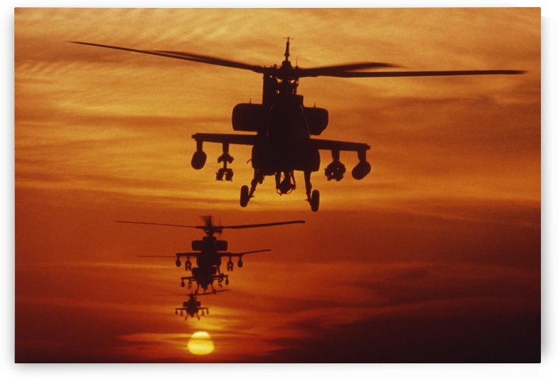 Four AH-64 Apache anti-armor helicopters fly in formation at dusk. by StocktrekImages