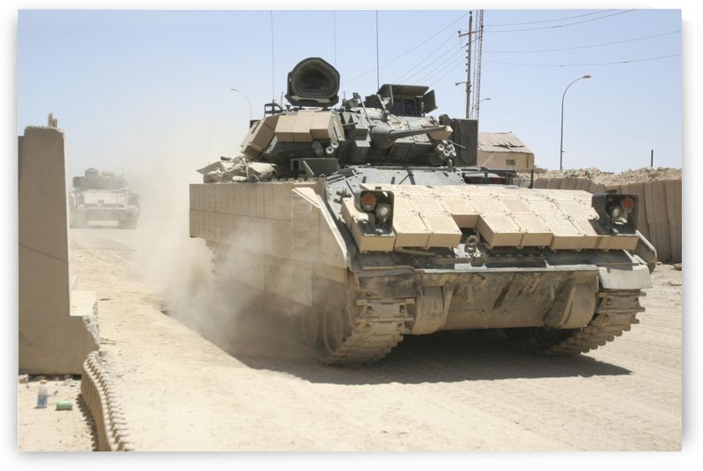 An M2 Bradley Fighting Vehicle patrols past Command Post Hit Iraq. by StocktrekImages