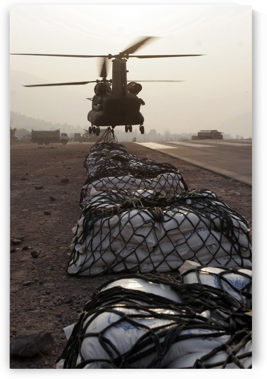 Marines attach sling loads to the body of an Army CH-47 Chinook cargo helicopter. by StocktrekImages