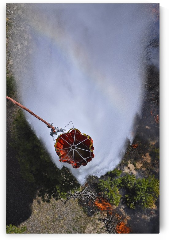 UH-60 Black Hawk helicopters perform water drops using Bambi Buckets. by StocktrekImages
