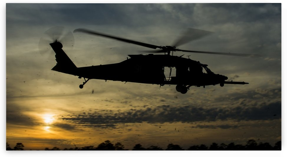 A U.S. Army UH-60 Black Hawk leaves the drop zone. by StocktrekImages