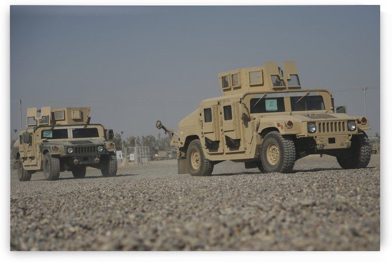 Two M1114 Humvee vehicles at Camp Taji Iraq. by StocktrekImages