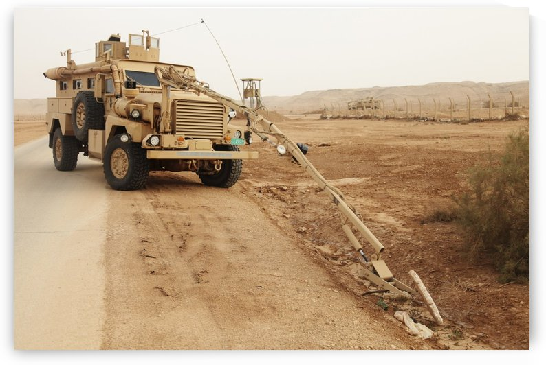 A MRAP vehicle disassembles an improvised explosive device. by StocktrekImages