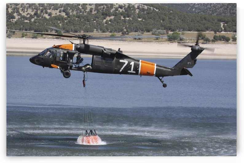 A U.S. Army UH-60 Black Hawk helicopter collects water from a reservoir. by StocktrekImages
