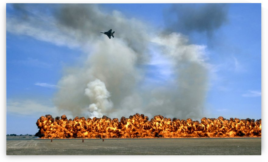 Pyrotechnics explode while an F-15 flies over to simulate an air-to-ground attack. by StocktrekImages