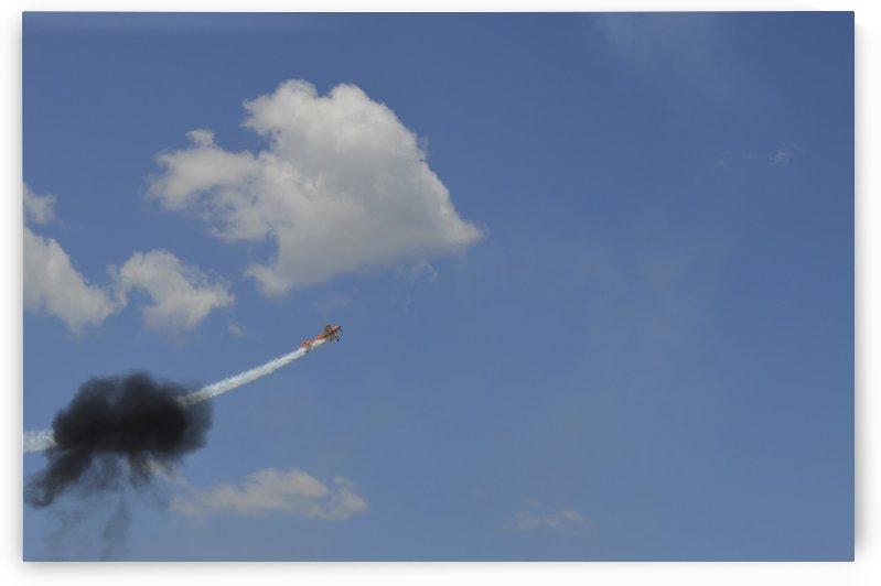 A Yakovlev Yak-55M aerobatic aircraft flys through a smoke ring. by StocktrekImages