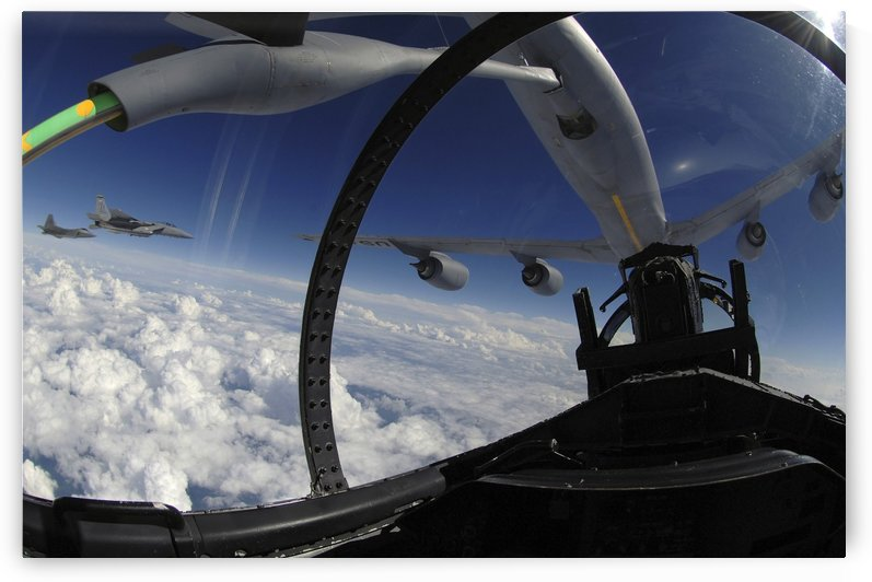 The refueling boom from a KC-135 Stratotanker arches over an F-15 Eagle as it refuels the aircraft. by StocktrekImages