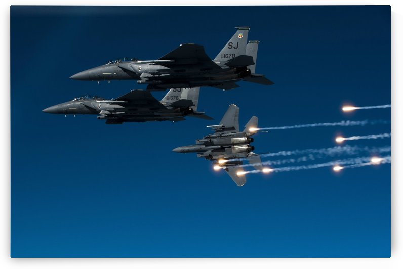 A F-15E Strike Eagle aircraft releases flares. by StocktrekImages