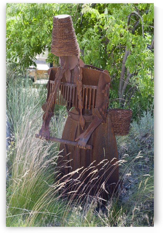 Metal sculpture of a woman harvesting grain seeds. by Bob Corson