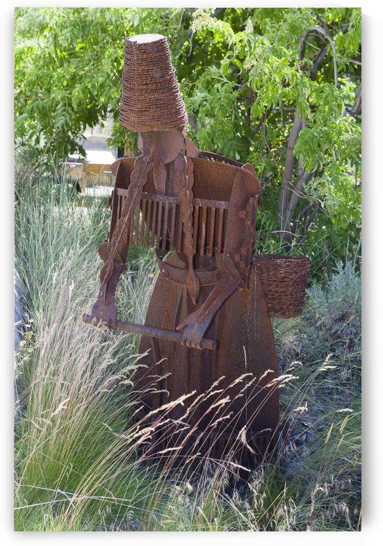 Metal sculpture of a woman harvesting grain seeds. by Bob Corson