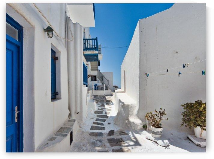 Narrow path amidst white houses by Pixelme ca