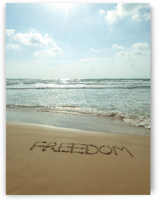 Word Freedom written in sand on the beach by Assaf Frank