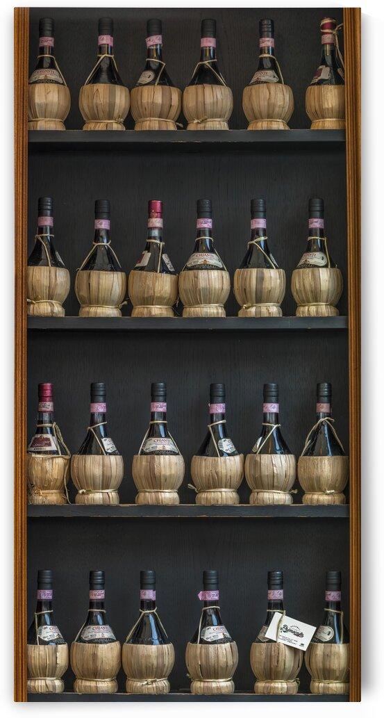 Old wine bottles on wooden shelf by Assaf Frank