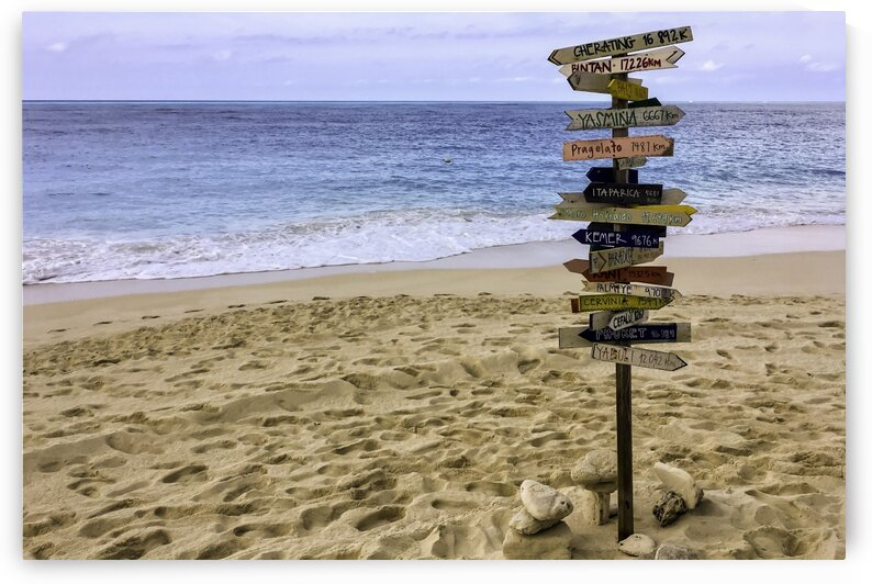 Direction sign on the beach by Daniel Ouellette
