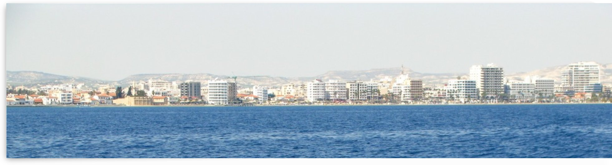 Cypriot shore of Larnaca with mountains in the back and modern buildings by Vlad Radulian