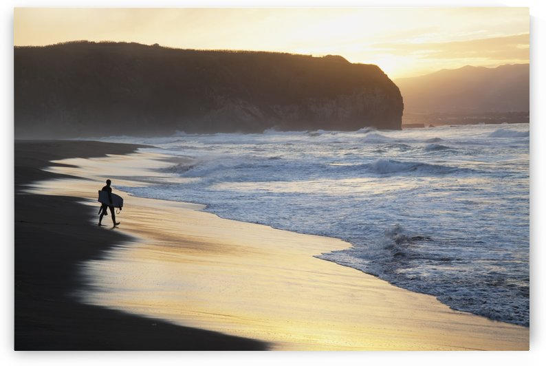 A surfer walks to the water at sunrise, Santa Barbara Island; Sao Miguel Island, Acores, Portugal by PacificStock