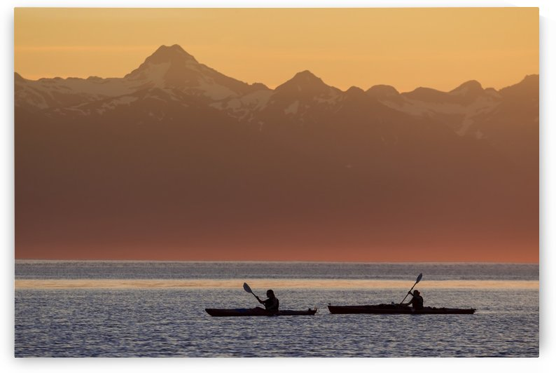 Two female sea kayakers enjoy a warm summer evening while paddling in Favorite Passage, Alaska, near Eagle Beach State Recreation Area, Juneau. Chilkat Mountains beyond. by PacificStock