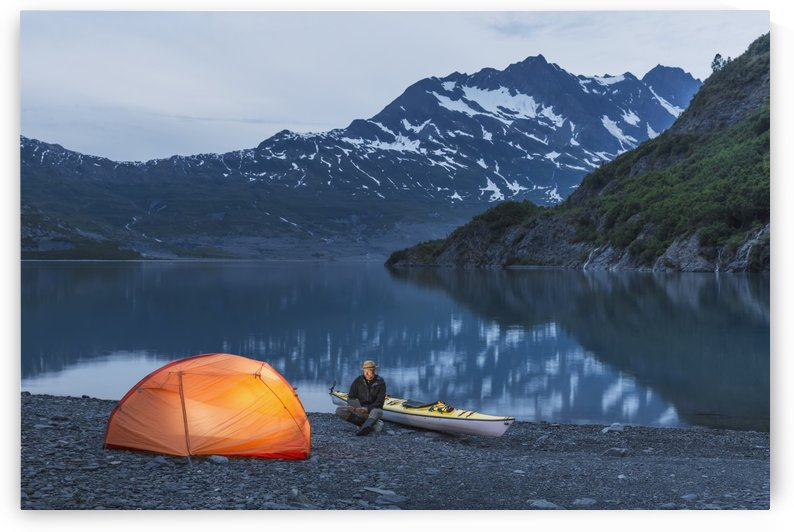 Man reading on a electronic tablet while camping with a tent and kayak at Shoup Bay State Marine Park, Prince William sound, Valdez, Southcentral Alaska by PacificStock