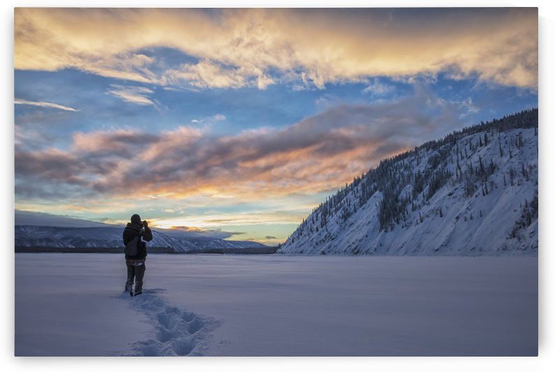 Photographer shooting the sunset over the Yukon River; Dawson City, Yukon, Canada by PacificStock