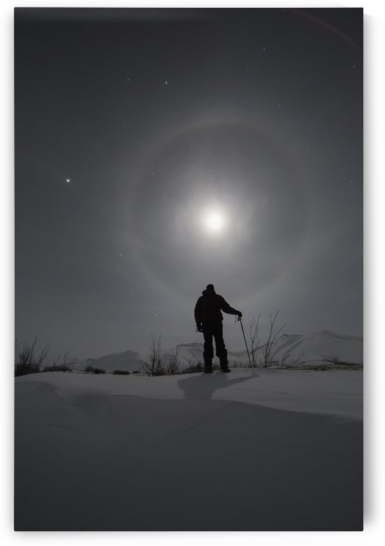 Man snowshoeing along the Dempster Highway under a moon glowing with rings; Yukon, Canada by PacificStock