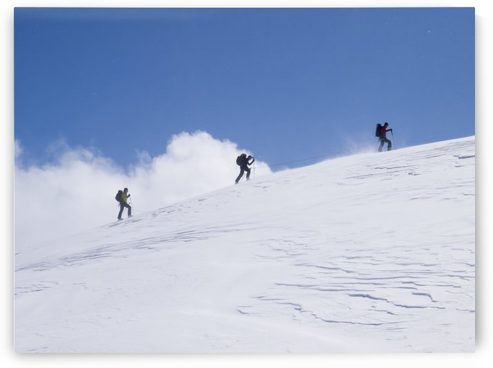 Three ski tourists walking to the summit; Switzerland by PacificStock