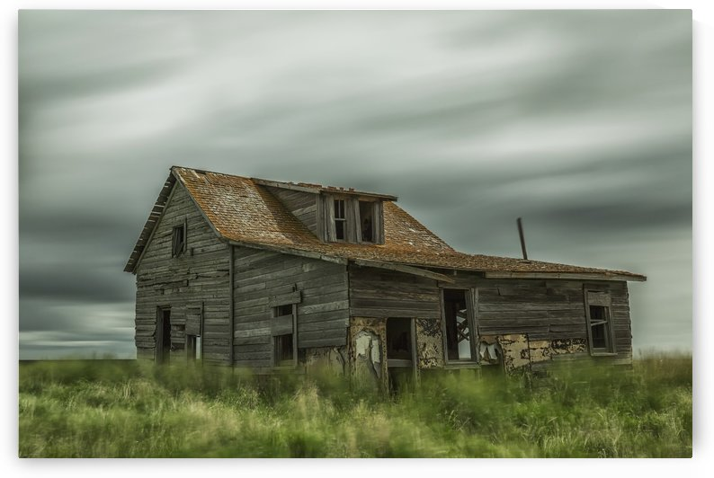 Long exposure of clouds going over an abandoned house; Val Marie, Saskatchewan, Canada by PacificStock