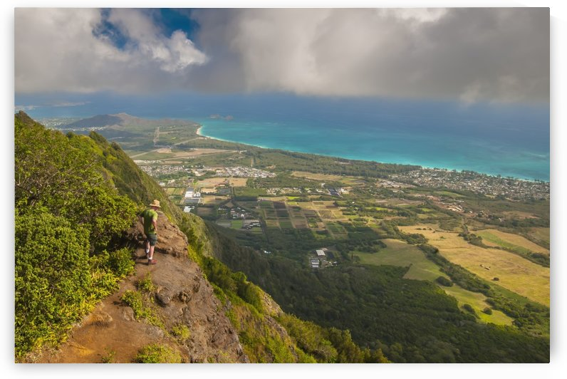 A man standing on the edge of a cliff on the Kuliouou Ridge Trial enjoys the view of Oahu's windward side and the town of Waimanalo as the clouds roll in on a summer's day; Waimanalo, Oahu, Hawaii, United States of America by PacificStock