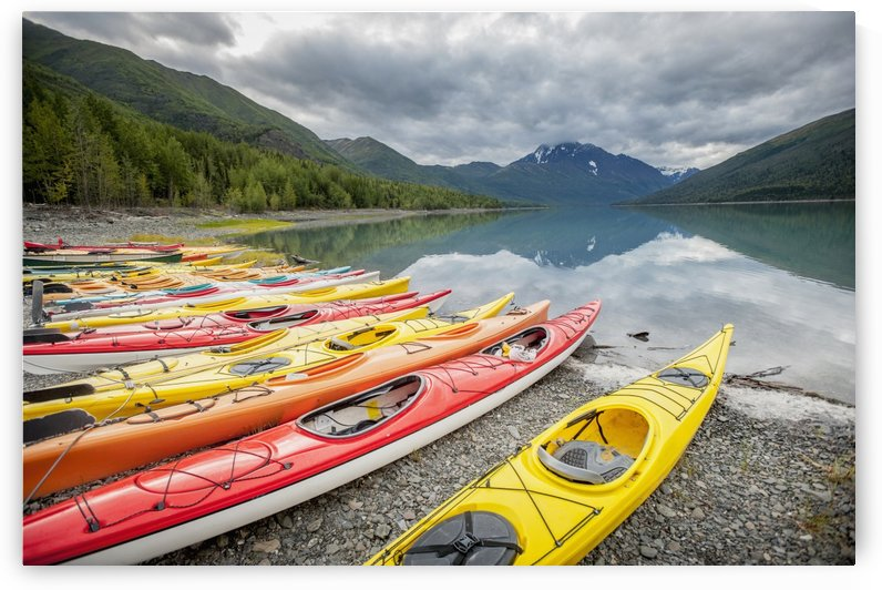 Kayaks in a row on shore at Eklutna Lake, Chugach Mountains, Southcentral Alaska. by PacificStock