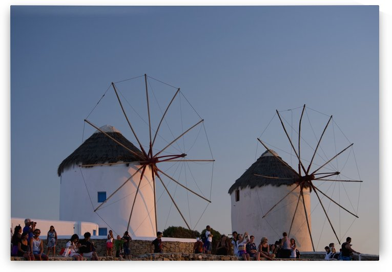 People watching the sunset beneath old windmills; Mykonos Town, Mykonos, Cyclades, Greek Islands, Greece by PacificStock