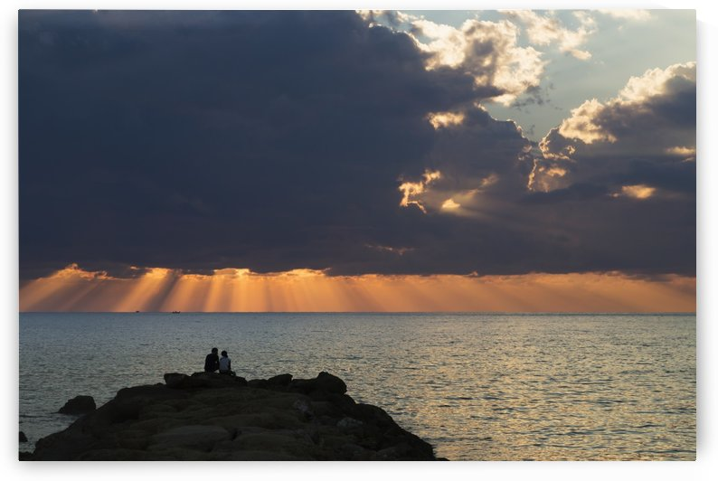 Dramatic sky with orange sun rays reaching down to the water on the horizon out of storm clouds; Paphos, Cyprus by PacificStock