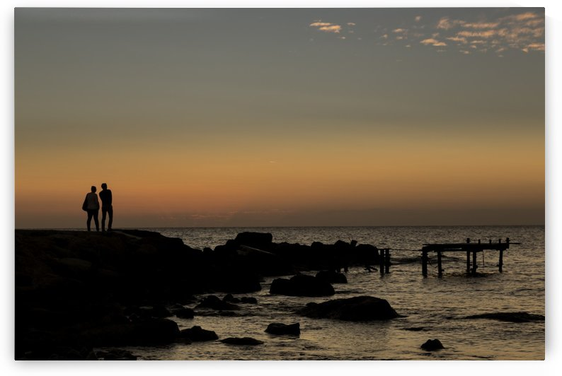 Silhouette of two people standing at the water's edge watching the sunset over the water; Paphos, Cyprus by PacificStock