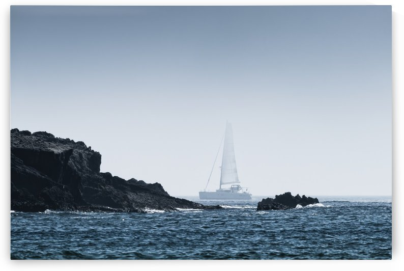 Rock on the rugged coastline with a sailboat in the fog; Tarifa, Cadiz, Andalusia, Spain by PacificStock