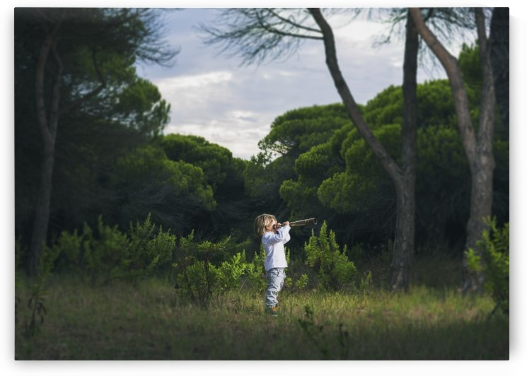 A young boy looks through a telescope standing in the grass; Tarifa, Cadiz, Andalusia, Spain by PacificStock