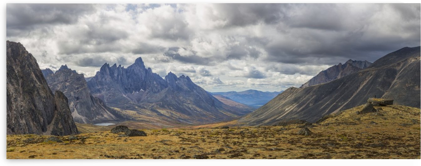 Men standing on a boulder in the distance in Tombstone Territorial Park in autumn; Yukon, Canada by PacificStock