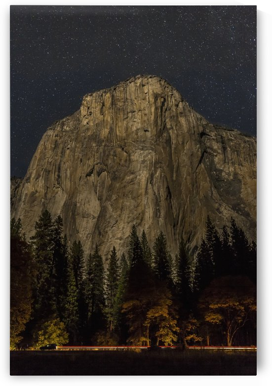 A vehicle drives along Northside Drive in front of El Capitan at night in Yosemite Valley, Yosemite National Park; California, United States of America by PacificStock