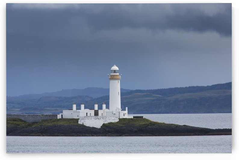 White lighthouse under storm clouds along the coast; Scotland by PacificStock